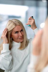 Blonde Frau steht vor dem Spiegel und betrachtet ihren grauen Haaransatz