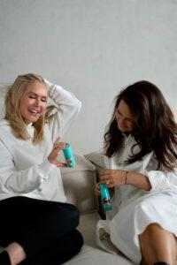Zwei Frauen sitzen auf einem Sofa und schauen sich Magic Retouch Flaschen an zum Retuchieren grauer Haare