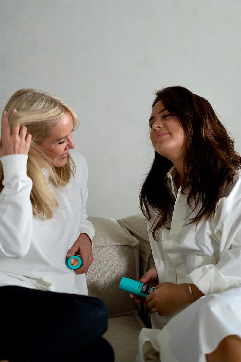 Zwei Frauen sitzen auf dem Sofa und unterhalten sich gut gelaunt