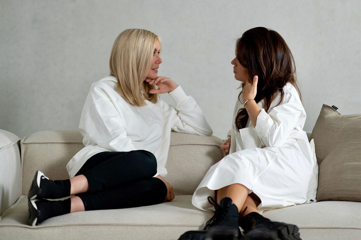 Zwei Frauen sitzen auf dem Sofa und unterhalten sich